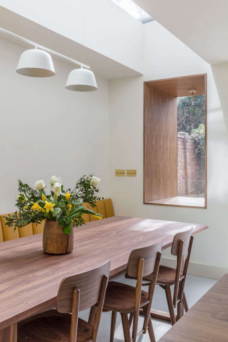 Walnut also frames the recessed window. Note the brass light switch covers: for something similar, see Beautiful Basics by Meljac.