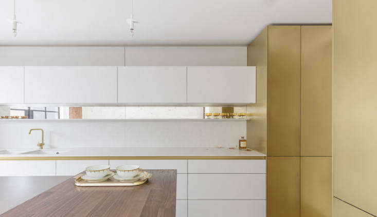 The design team stuck to a palette of white, brass, and walnut. All of the components are bespoke.