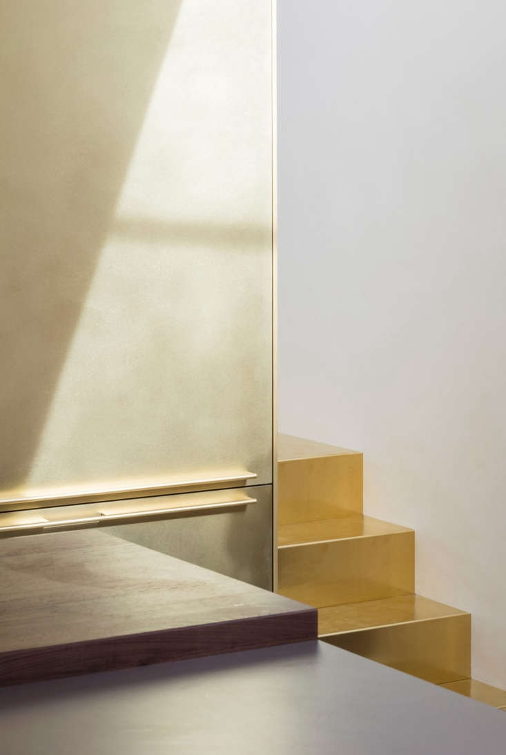 The brass detailing extends to the fridge and freezer pulls, and the stairs.