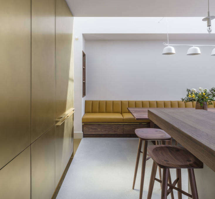The fridge and pantry are incorporated into a storage wall faced in brass. &#8