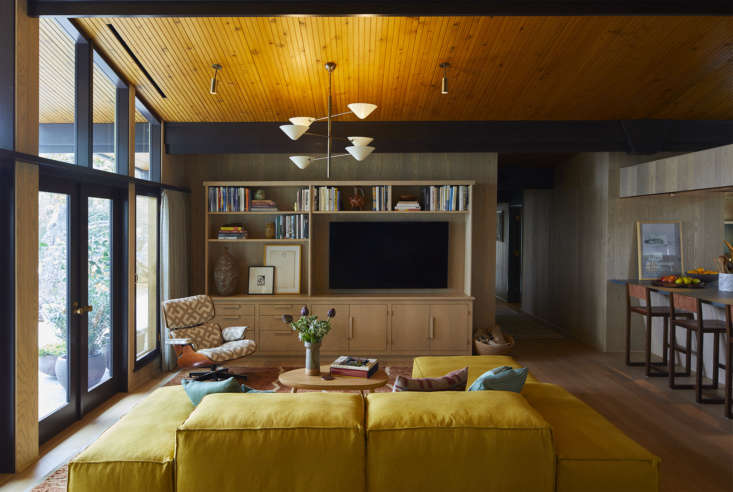 The family room, across from the kitchen, is the focal point of the home. A palette of teal, yellow, and rust runs throughout.