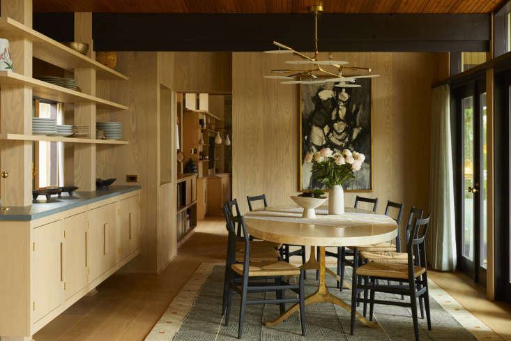 In the dining room, a brass Lindsey Adelman chandelier hangs over the Bronze Wishbone Table by BDDW.