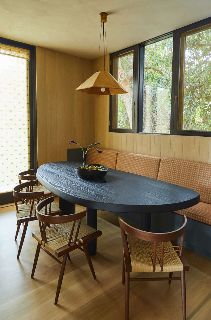 A vintage cork pendant light by Wilhelm Zannoth Zanotl hovers over the dining table. The chairs are by George Nakashima.
