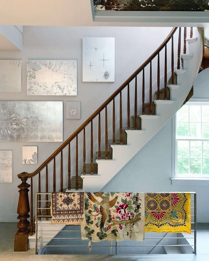 Amy and Jim removed the wall that concealed the back stairs. In its place, a modern railing adorned with colorful textiles. &#8