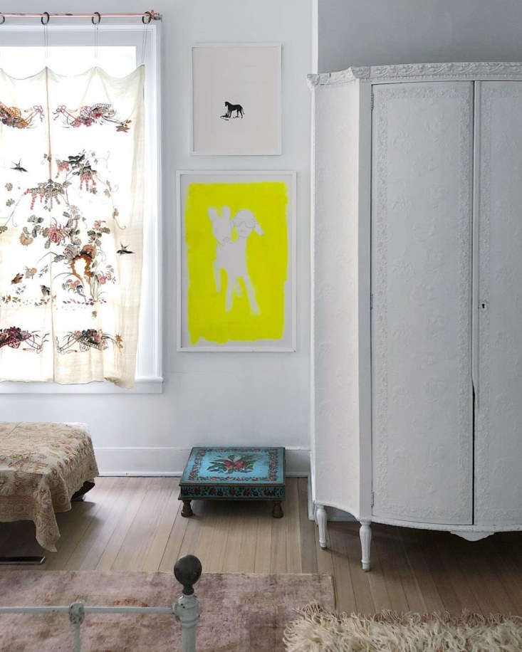 In their bedroom, an Art Nouveau tooled leather-covered armoire, painted white by Amy more than  years ago, houses their television. The neon yellow art of the couple as a two-headed creature is by Jim.