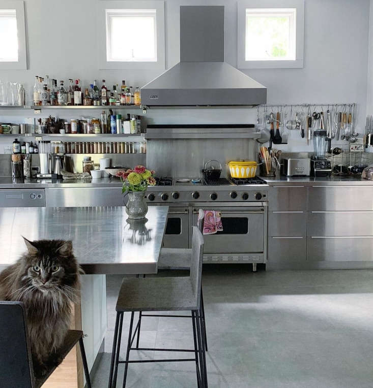 Adjacent to the dining room is the stainless steel kitchen, presided over by McCabe, a Maine Coon. The floors in this part of the home are made up of 3- by 7-foot porcelain tiles that resemble concrete.