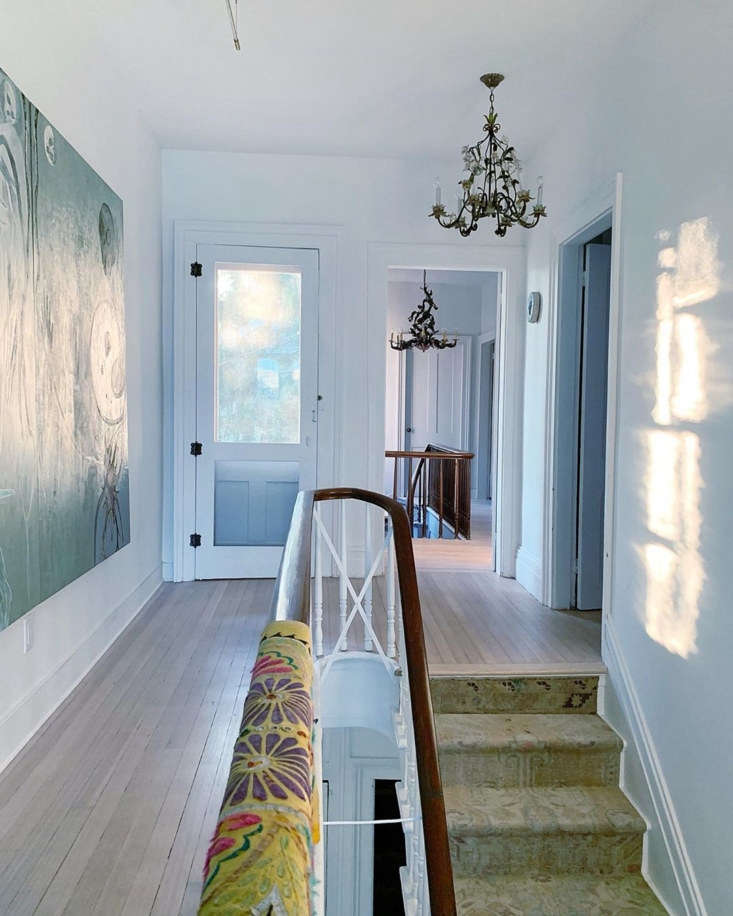 The second floor landing with both sets of stairs visible. The wood floors are all original to the home. Amy and Jim had them sanded, then &#8