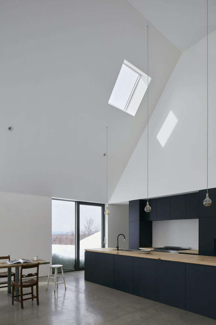 The interior is composed of minimalist double-height spaces with polished concrete floors, white walls, skylights, and wooden accents. The entry leads to the combined kitchen, dining, living area. The ceiling here rises for  feet.