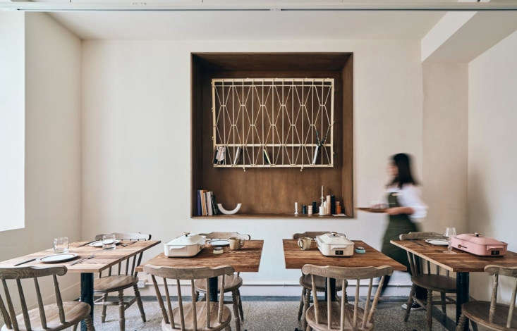 A salvaged window grill is hung in a niche alongside tables for two with  griddles for making Home Home&#8