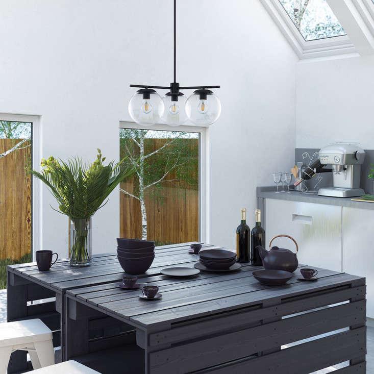 Linea's Caserti Midcentury Modern Three-Light Hanging Chandelier in black ($99.99) draws attention to a dark kitchen island. It&#8