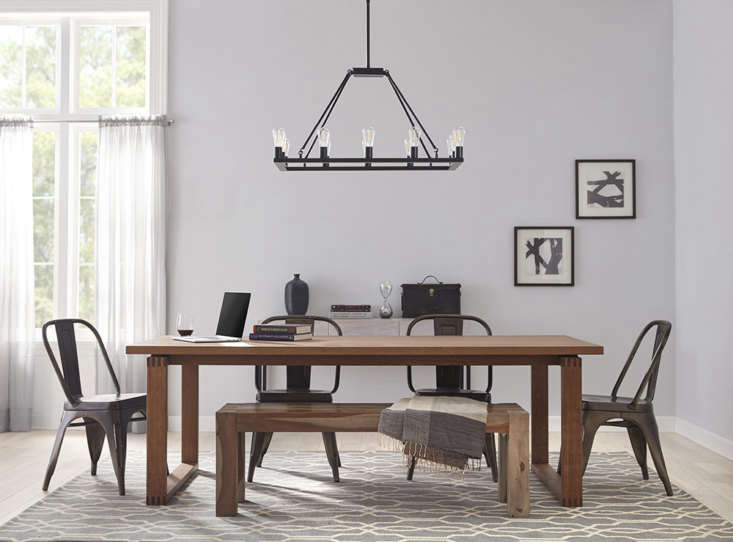 Proof that lighting can help define a space: An industrial-style Sonoro Rectangular Chandelier ($9.99) echoes the shape of both table and rug, creating the feeling of a room within a room.