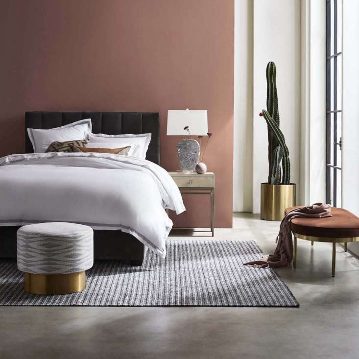 The hand-sewn Butler Channeled Tufted Platform Bed, shown here in graphite velvet, adds long-lasting luxury to the bedroom. At the foot of the bed is the petite Margaux Swivel Ottoman in silver Taos fabric.