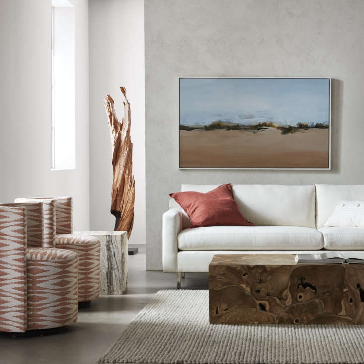 The lounge-like Hunter Sofa is designed with comfort in mind and is available in a wide selection of fabrics, including low-maintenance Sunbrella performance fabric, shown here. Alongside is the Tremont Rectangular Cocktail Table, crafted from reclaimed teak roots salvaged from trees harvested for lumber. And at left, the petite Poppy Swivel Chairs.