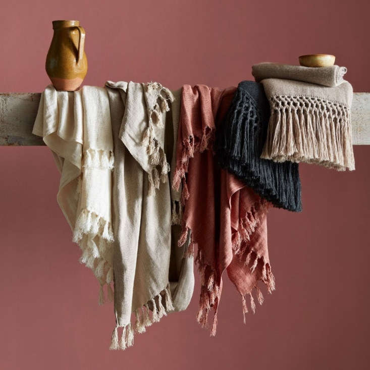 New Linen Flax Throws in clay, flax, and cream are made from one hundred percent linen. On the right are lightweight but warm fringed Alpaca Macrame Throws in charcoal and driftwood.