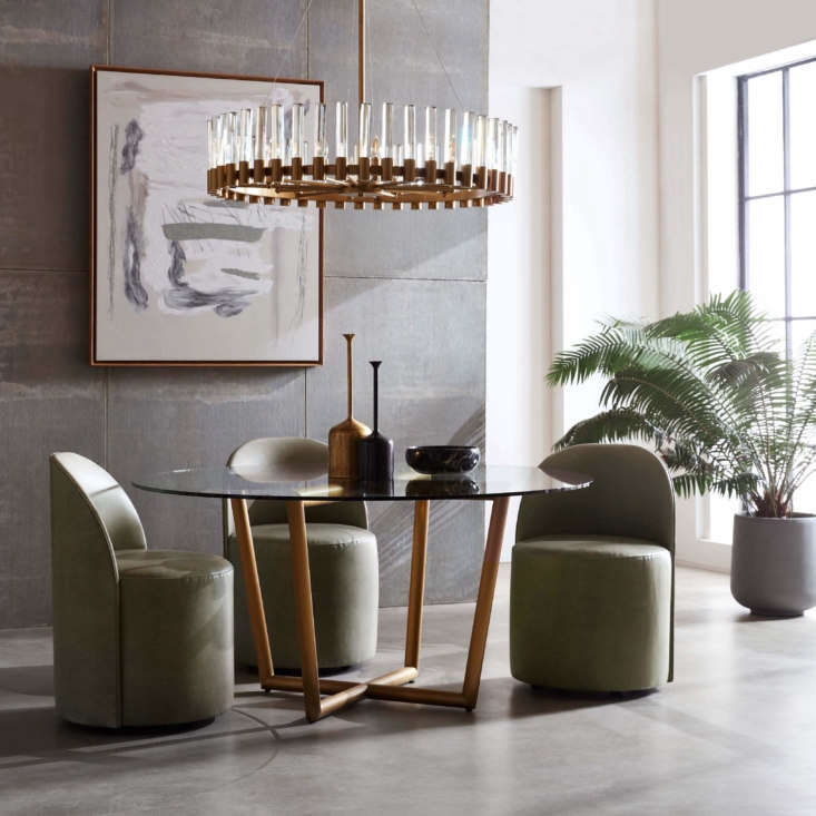 The Margaux Side Chairs are comfortably curved and set on casters for ease of movement; the rich Moore & Giles leather shown here, called Mont Blanc Fern, will patina over time. The chairs are set around the Modern Round Dining Table, which is available in a range of sizes, finishes, and tabletops, with a Perla Chandelier overhead.