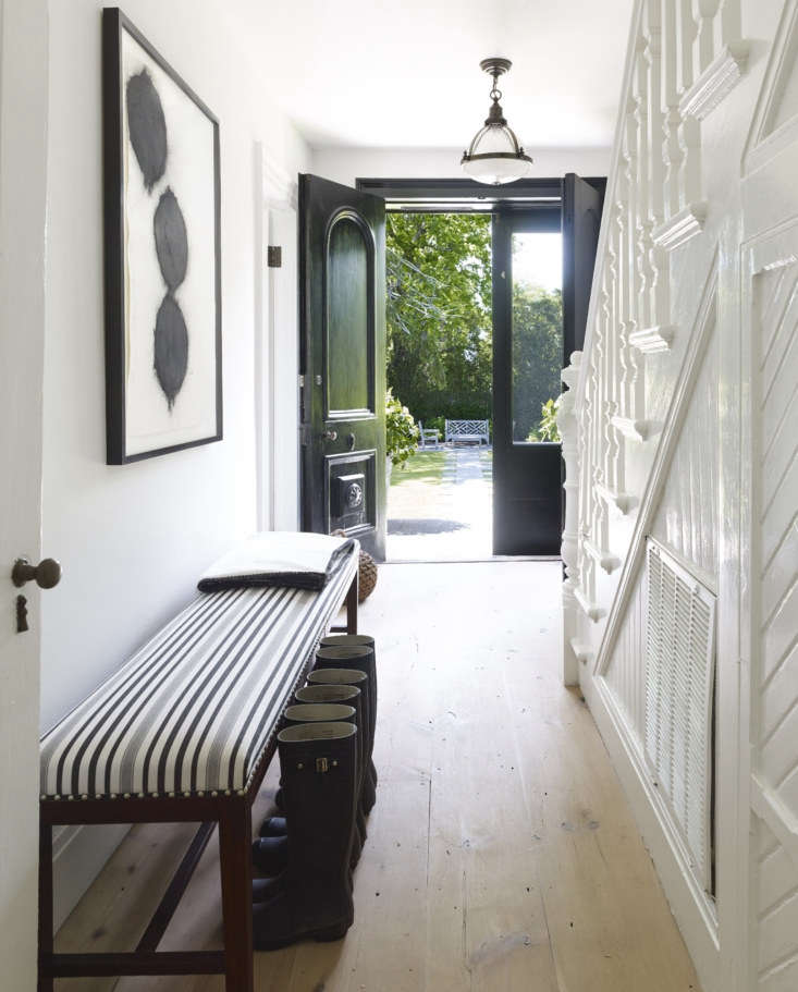 Double front doors open to a hall with a new pine floor and a grand stair cloaked in white: the couple used Benjamin Moore&#8