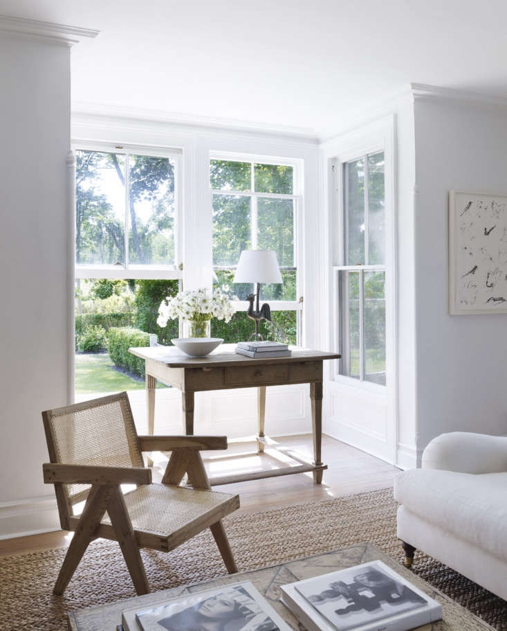 A bay window overlooks the garden. The Jeanneret teak Chandigarh chair is one of two from Bloom. The rug is Bloom&#8