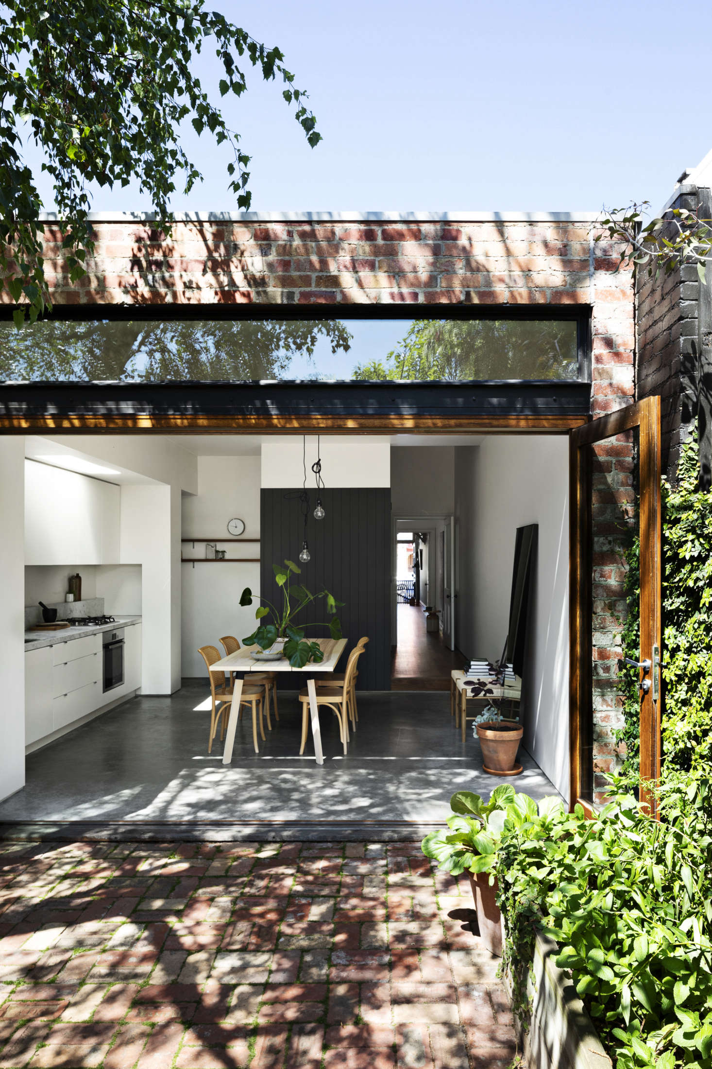 The center of the house is a bright kitchen and dining area with custom bifold doors and a transom window that fully connects indoors to out. The shotgun hallway was created by flipping the position of the original hall. The charcoal paneled partition hides the fridge and laundry.