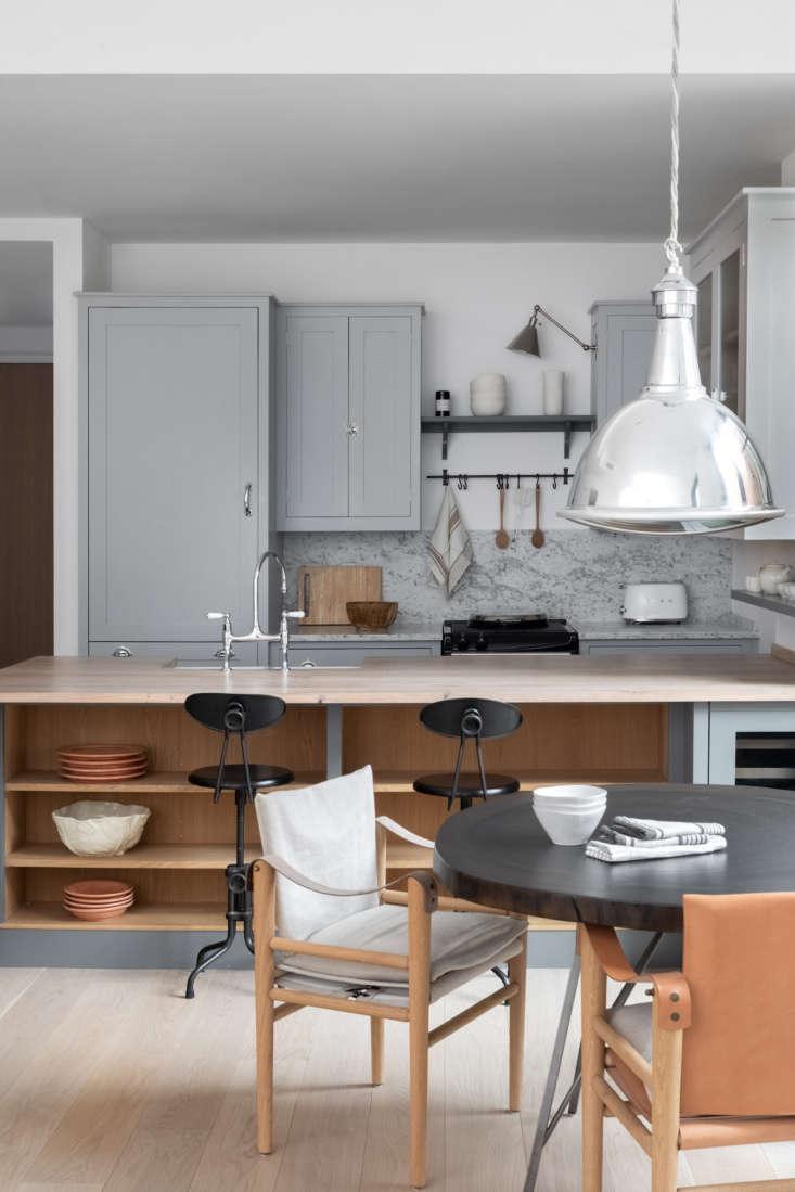 Sillas de cuero y lona escandinavas rodean la mesa del comedor.  Para una apariencia similar, pruebe Kaare Klinte & # 8
