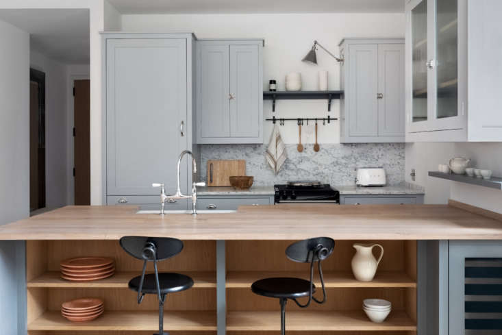 Raw oak open shelving in the peninsula adds a warm counterpoint to the cool palette.