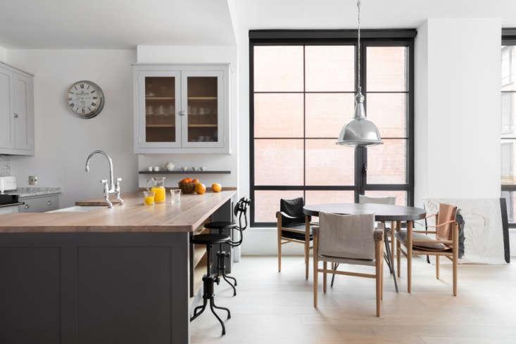 La cocina es compacta y ancla un extremo de una espaciosa sala de estar de planta abierta.  Las ventanas de gran tamaño proporcionan mucha luz natural.