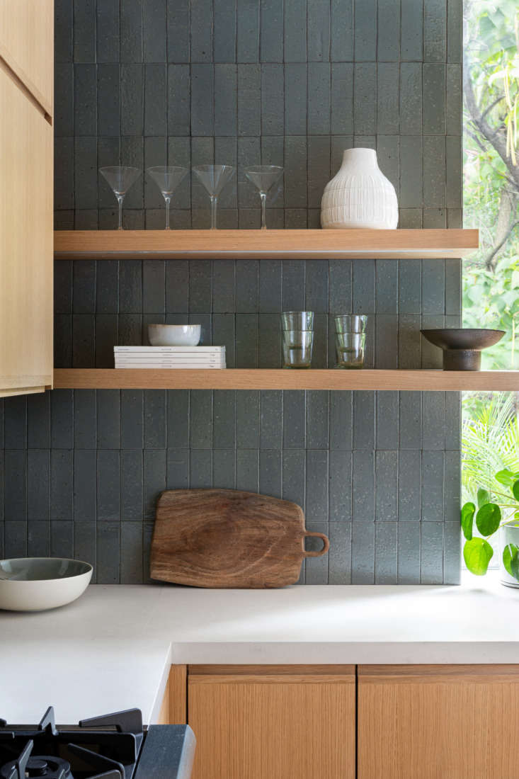 Textural Thin Brick Tiles from Clé serve as backsplash and backdrop for the open shelving next to the sink.