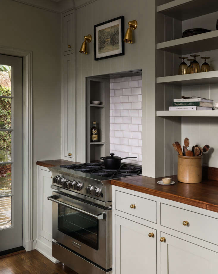 the blue star range is set in a niche with built in storage. the handmade crack 18
