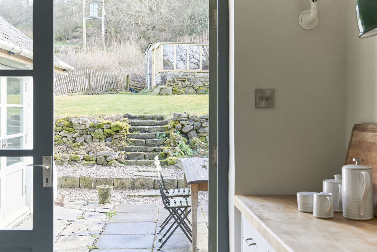 French doors lead to a patio. The trim in the kitchen is painted Farrow & Ball&#8