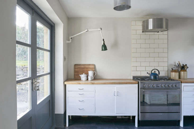 The wood countertops are made from a beech tree that felled near their property. The slim range hood is from Ikea, &#8