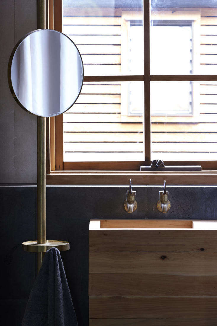 The bathroom has a homemade cypress sink and one of the cypress-framed windows that replaced the existing aluminum ones. The mirror is cleverly positioned on a standing brass valet that also incorporates a small table and towel hook. &#8