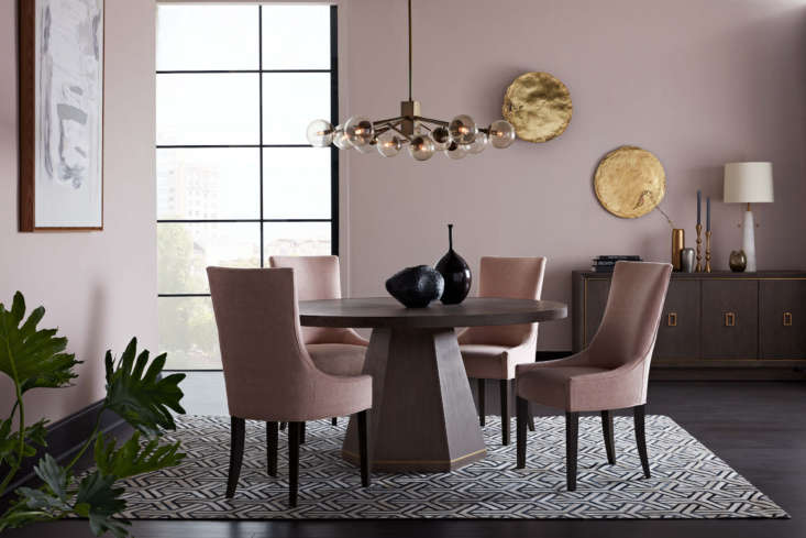 The company's Emerson Round Dining Table—part of the new Emerson dining table collection—features open-grain oak veneers and brushed brass accents. Around it are the Ada Side Dining Chairs in a Sunbrella fabric called Costa-Blush. Overhead is the brass and smoky glass Savoy Chandelier.
