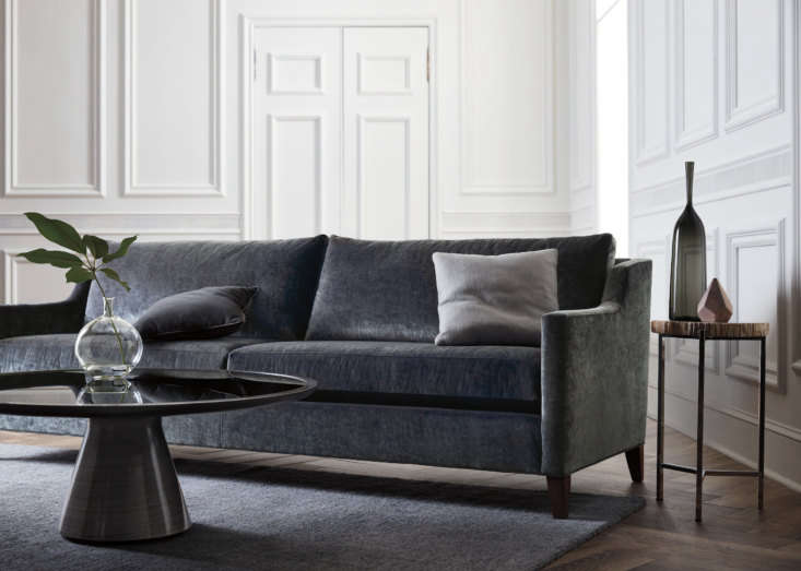 The Gigi Sofa—shown here in slate velvet—offers a modern feel to a traditional silhouette, with comfortable plush cushions, French seams, and tall tapered legs for a clean look. It's available in hundreds of fabrics and leathers and two widths, and can also be fitted with a fabric skirt for a more traditional look. It pairs well with the Addie Cocktail Table in a hand-applied, brushed-metallic finish—this one is pewter—and black-glass top.