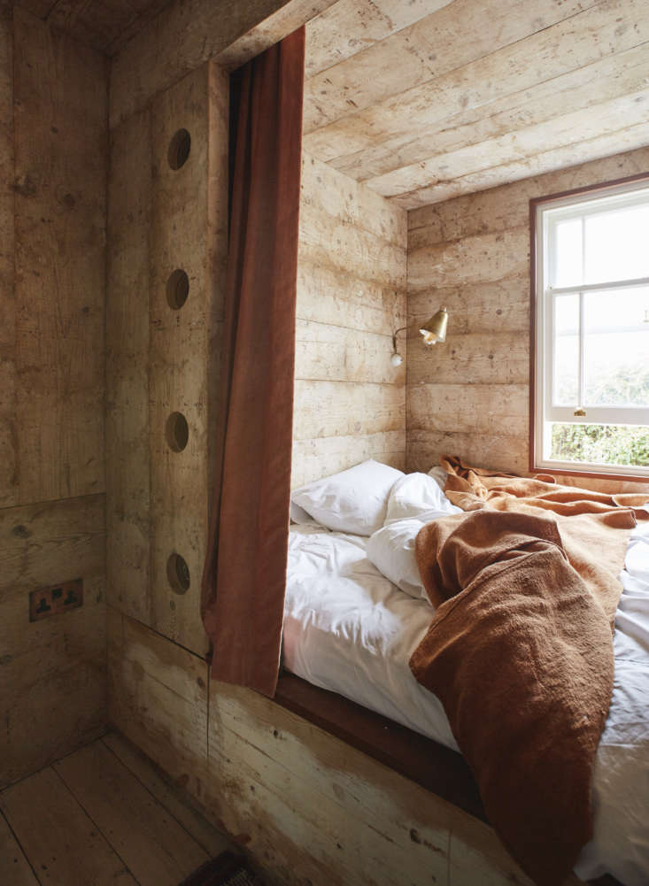 In one of the guest rooms, the bed is set in a nook paneled in reclaimed pine cheese boards (a longstanding Retrouvius speciality, these were used for maturing cheeses, hence the faint circular patterns, but, Maria assures, are odor free). The cutouts are small glass windows.