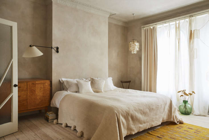 The master bedroom has limewashed walls and original moldings. The rug is Swedish. Note the 30&#8