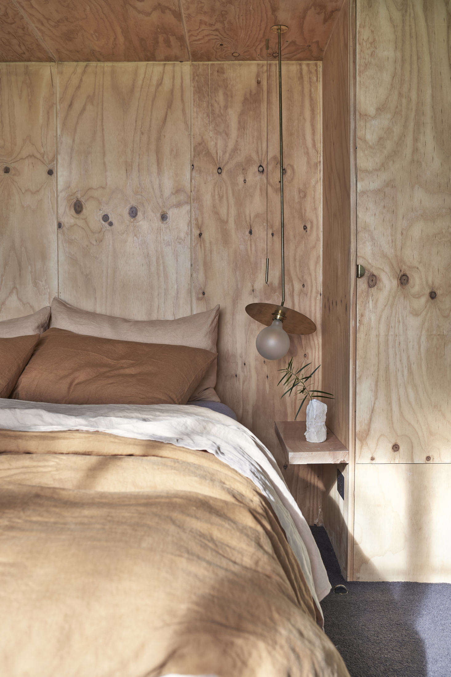 The bed is inset in a knotty plywood niche with an integrated closet on one side.