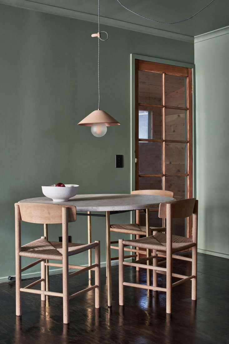 The combination of soft green and pale wood continues in the dining area. &#8