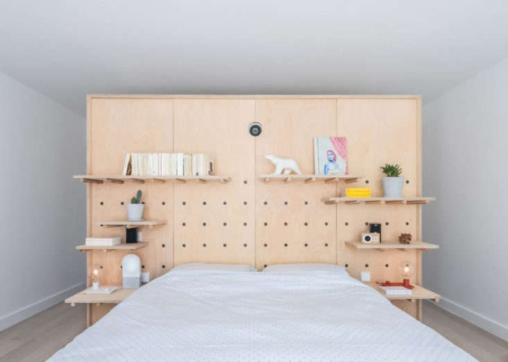 A cleverly designed pegboard-cum-headboard in the master bedroom. It conceals closets behind it.