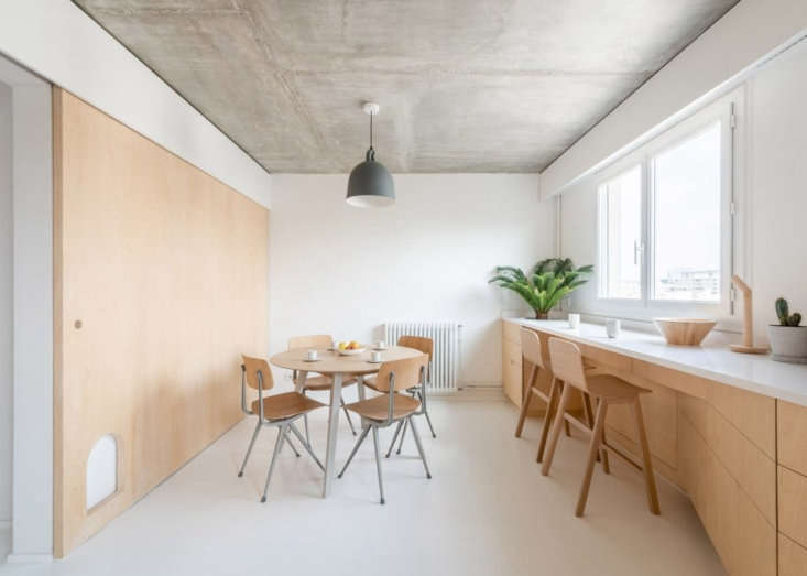 The breakfast nook, opposite the kitchen, with views of the th arrondissement. The Result Chairs are from Hay. A Grain Pendant Light from Muuto hangs over the table.