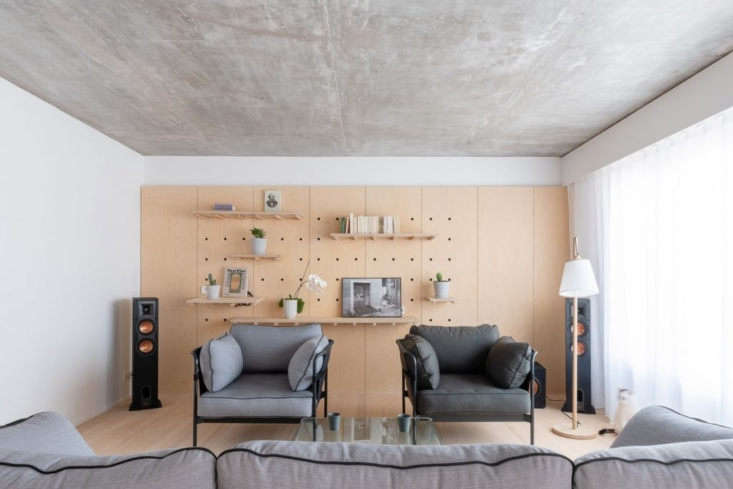 Pegboard walls appear in the living room, entrance, and master bedroom for flexible storage and display. The Can Sofa and Armchairs are by Ronan & Erwan Bourollec.