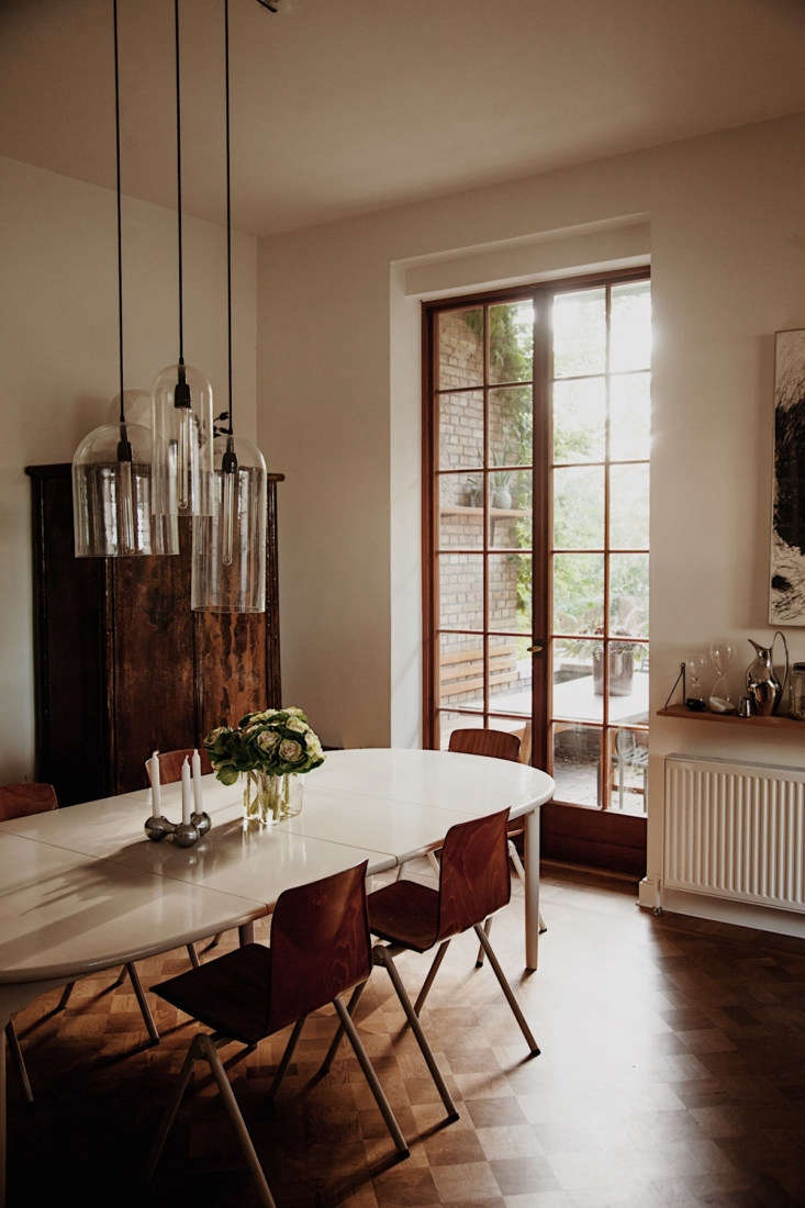 Susanne fashioned the pendant lights from glass cloches. The table is a Hans Wegner that she had painted after it sustained some water damage.