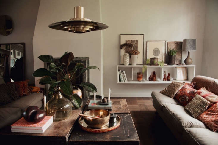 A quartet of four square tables makes for a giant coffee table, over which hangs a Louis Poulsen pendant light.