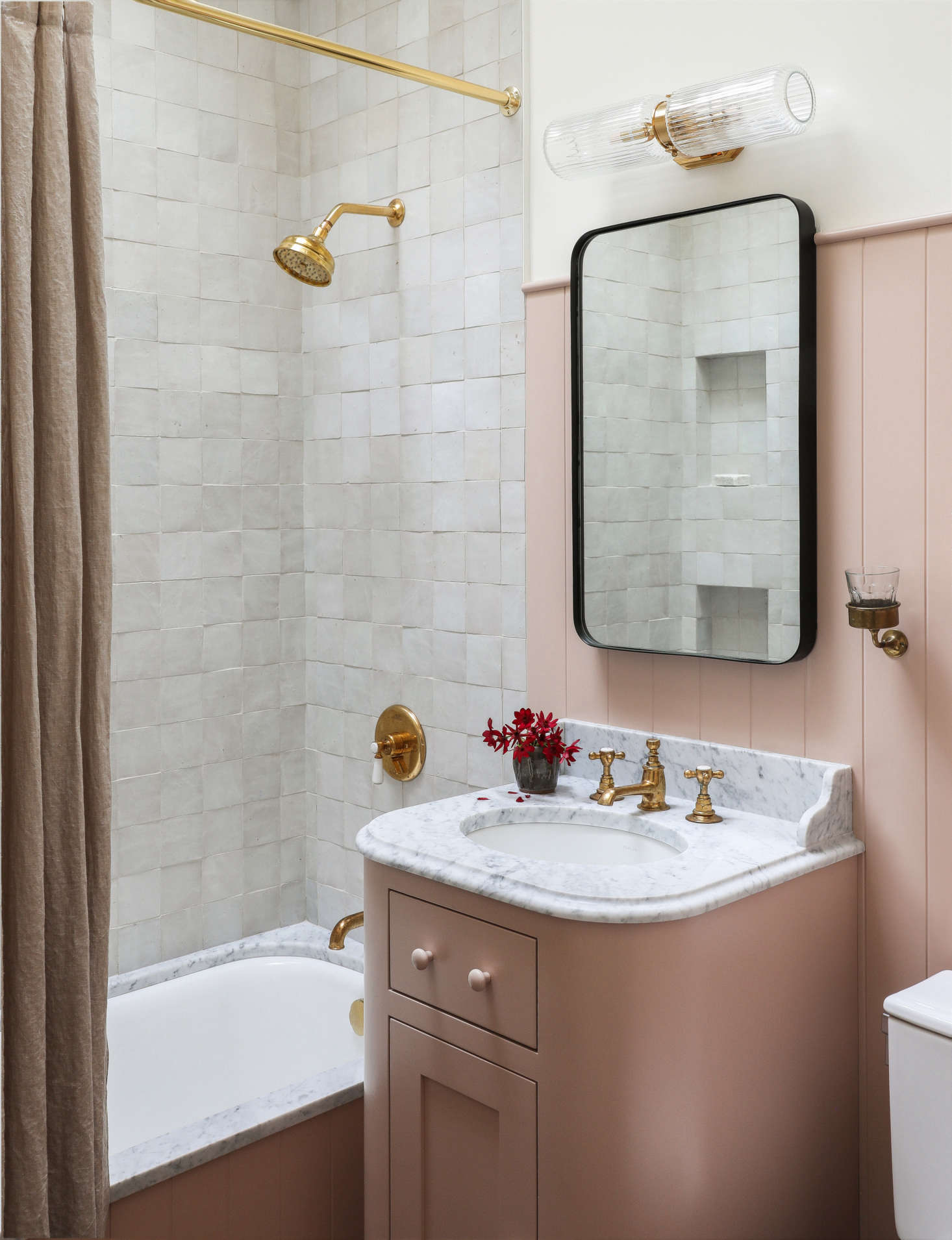 The same vertical paneling applied in the kitchen appears in the overhauled tiny main bath, where a custom pink vanity stands alongside a five-foot-long tub, all painted Farrow & Ball Setting Plaster. &#8