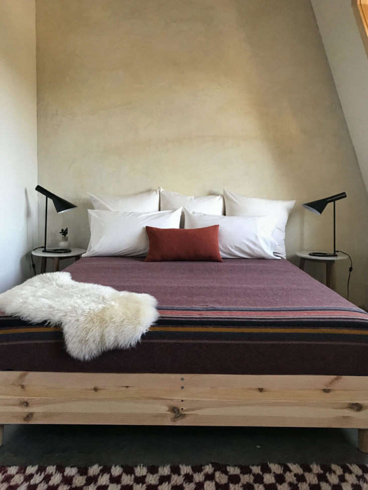 Above A tucked-under-the-eaves bedroom with Arne Jacobsen Table Lamps, an Ikea bed frame, and L.L. Bean camp blanket. Photograph by Hovey Design.