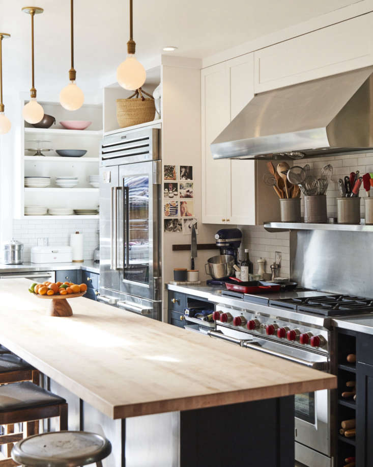 Other restaurant kitchen-inspired touches include a speed rack (to the left of the stove), dedicated cubbies for rolling pins (to the right of the stove), and open shelving for easy access to tools. Phyllis notes that having open storage may not be for everyone. It requires &#8