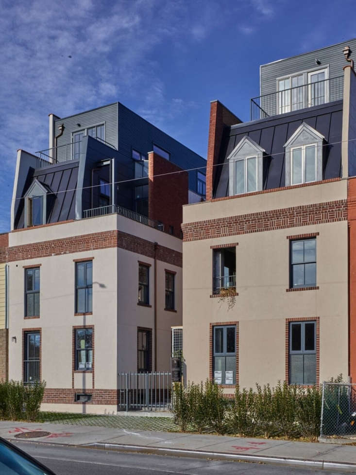 The buildings have their original brick, now faced with fiber-cement HardiePlank siding. The new top floors have standing-seam metal mansards with wood-clad &#8