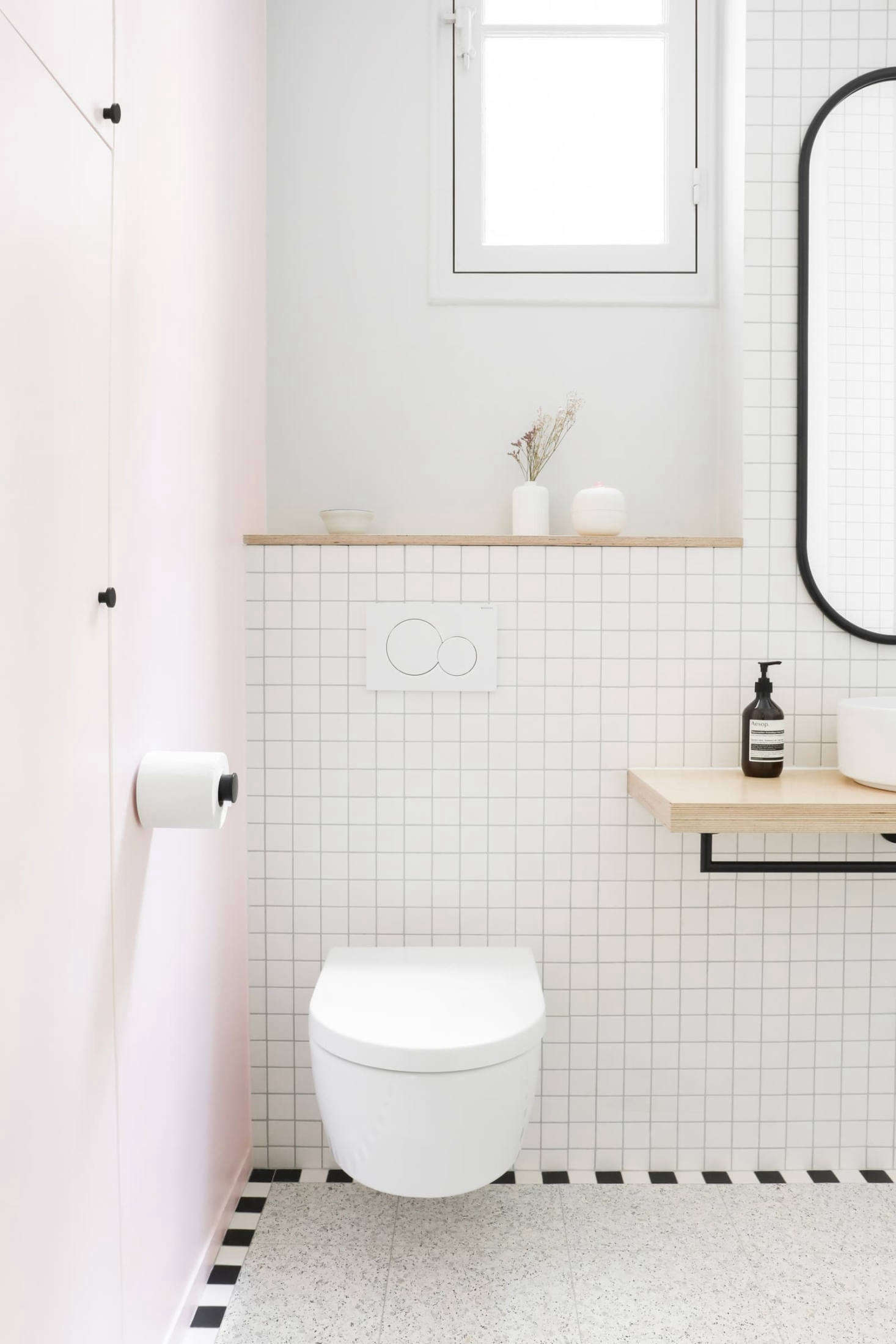 Pale pink reappears on the entry wall. To keep the space feeling open, the architects selected a wall-hung Villeroy & Boch toilet and designed a birch ply shelf for the sink &#8