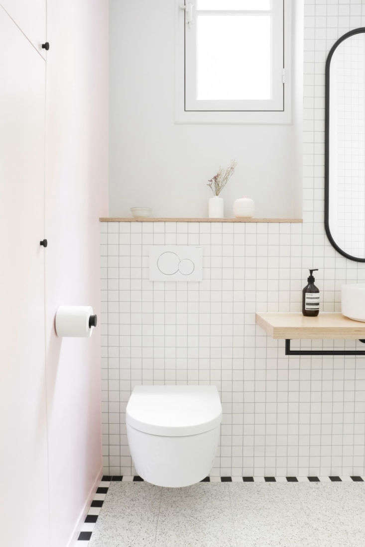 A Classic Paris Apartment Gets a ColorBlocked Update for Two Graphic Designers Pale pink reappears on the entry wall. To keep the space feeling open, the architects selected a wall hung Villeroy & Boch toilet and designed a birch ply shelf for the sink &#8\2\20;so both are suspended and the floor is the main element.&#8\2\2\1; The black hardware, toilet roll holder included, is from Paris department store Le BHV. The oval mirror is the Angui by AYTM.