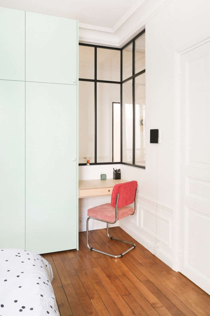 Hélène and Julien tucked a work niche next to the cabinets, and inserted an interior corner window that visually enlarges the space and brightens the hall. &#8