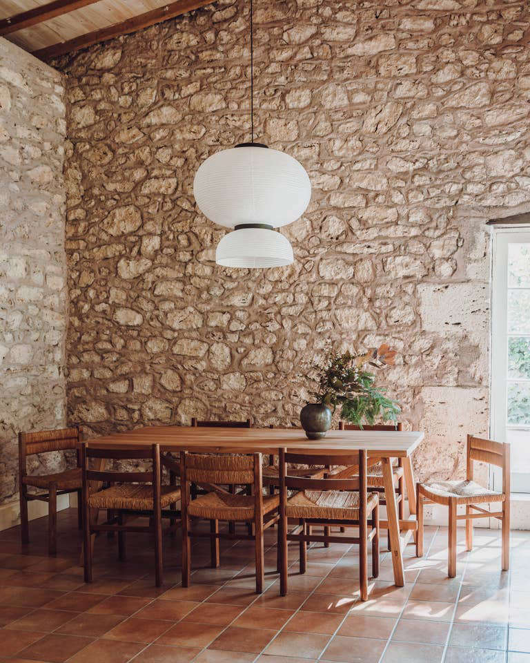 Double-height ceilings in the living and dining rooms. The Formakami JH5 Pendant Light from &Tradition hangs over the dining table.
