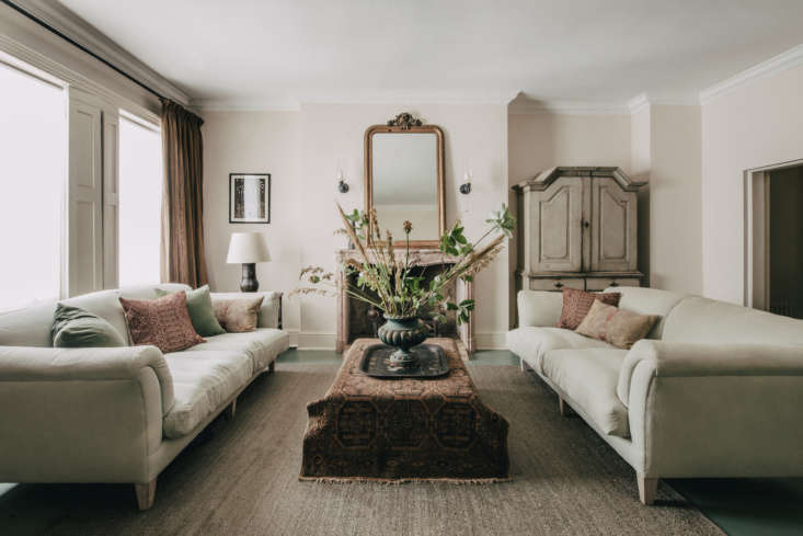 Perfect symmetry in the living room thanks to a pair of sofas, upholstered in pale green linen, from Lorfords. A flea market rug thrown over a coffee table is a bohemian touch in this otherwise traditional room.